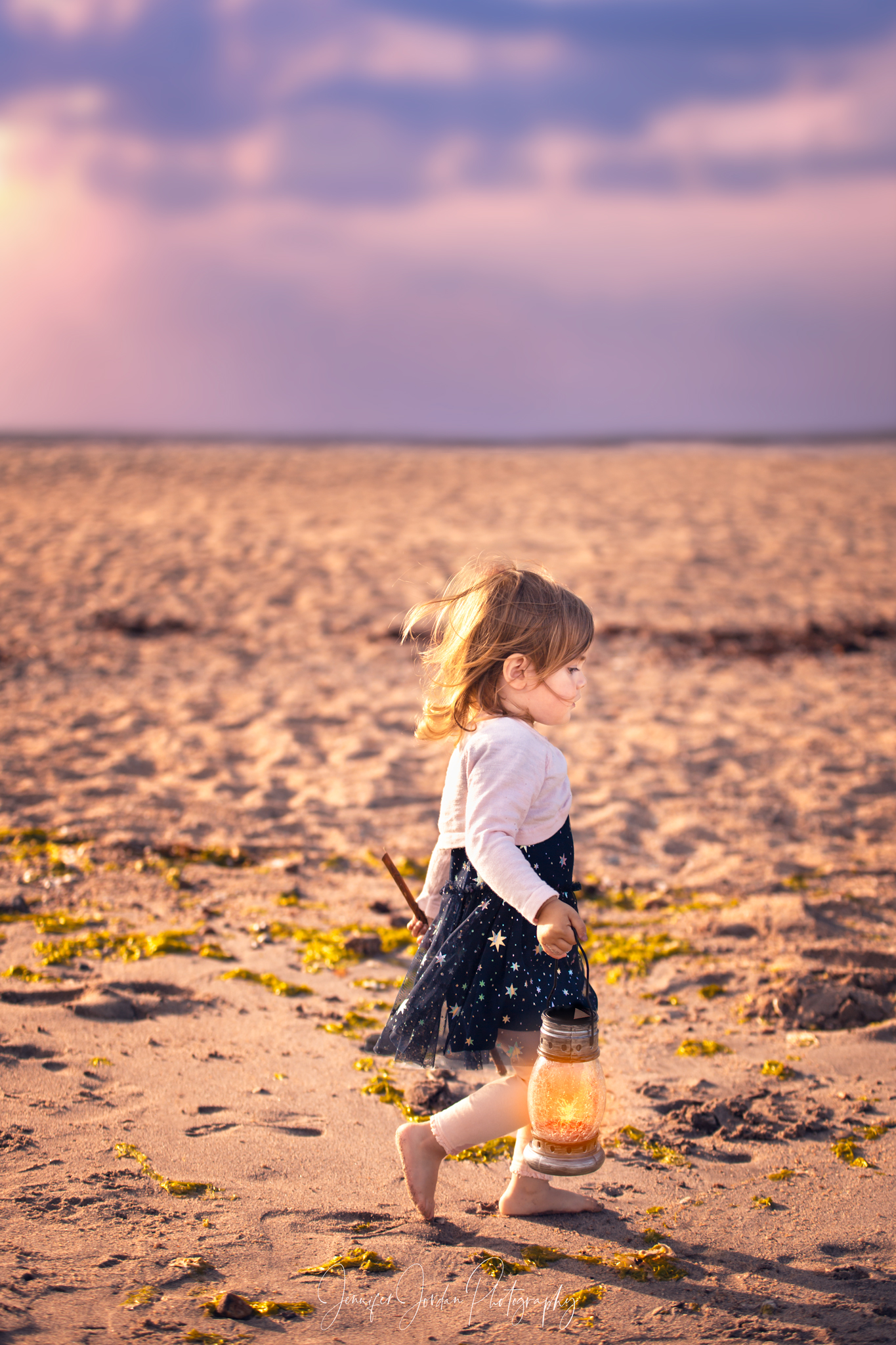 Creative imagery by Jennifer Jordan Photography. A little girl stands on the beach with a lion