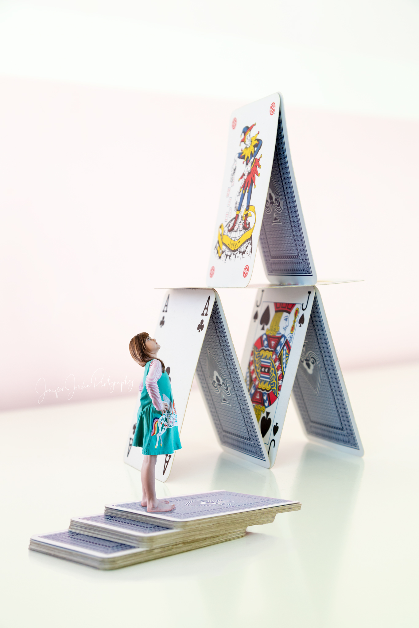 Creative imagery by Jennifer Jordan Photography. Little girl builds a giant house of cards.